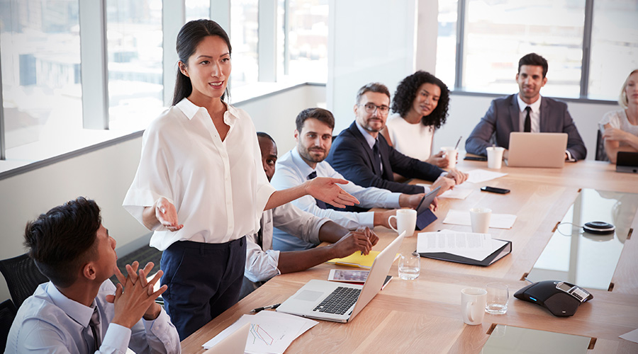Women standing up and speaking to her work colleagues at a business meeting